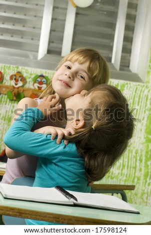 The children are in a school room.  They are holding each other like the are friends.  Vertically framed shot. - stock photo