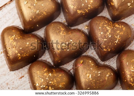 The chocolate candies decorated with edible gold powder on white wooden table - stock photo