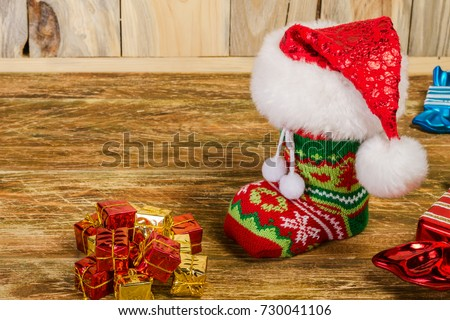 The Christmas stocking, covered with Santa's cap, is on a scratched wooden table. Nearby lie decorative candy and a hill of gifts. Copy space. Close-up.