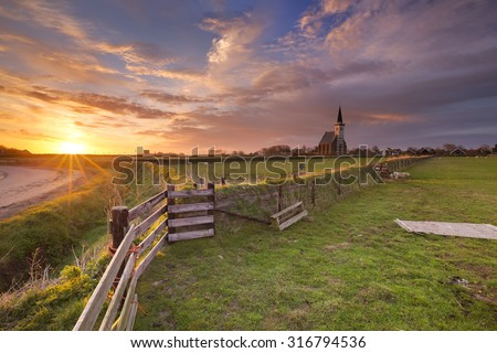 The church of Den Hoorn on the island of Texel in The Netherlands at sunrise. - stock photo
