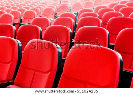 The cinema is neatly arranged in red seating, modern interior indoors.