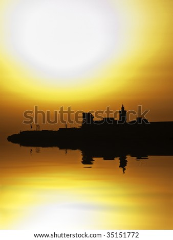 The Citadel in Gozo silhouetted by the setting sun - stock photo