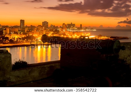 The city of Havana at night with an old spanish cannon on the foreground - stock photo