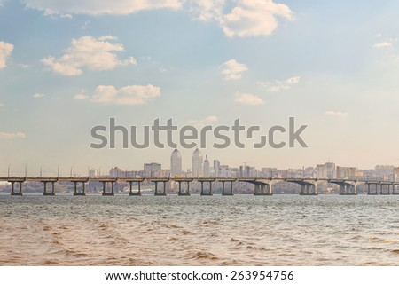 The city on the banks of the river with a view of the bridge and cloudy sky - stock photo