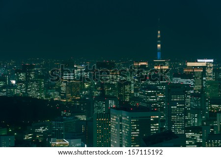The cityscape of Tokyo at night, with the Tokyo Skytree in the far distance. - stock photo