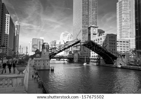 The Clark Street bridge on the Chicago River is raised to allow the passage of sailboats on the final sail of the season from their harbor in Lake Michigan to their winter dry dock destination. - stock photo