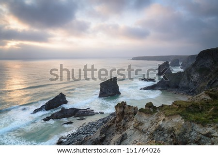 The cliffs and beach at high tide at Bedruthan Steps also known as Carnewas in Cornwall - stock photo