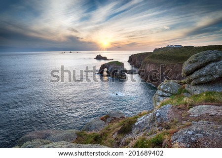 The cliffs and sea arch at Land's End in Cornwall - stock photo