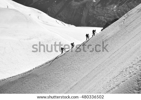 The climb. Climbers traverse the snow covered mountain