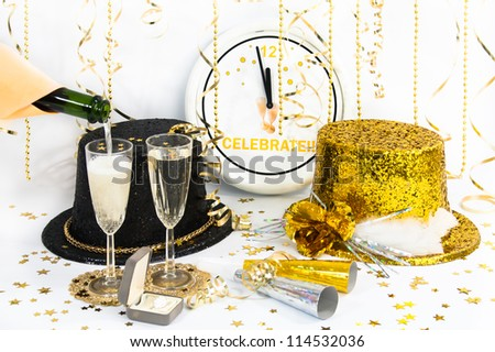 The clock has almost reached midnight and glittered hats, party horns, champagne in flutes and a diamond ring are ready for the celebration. - stock photo