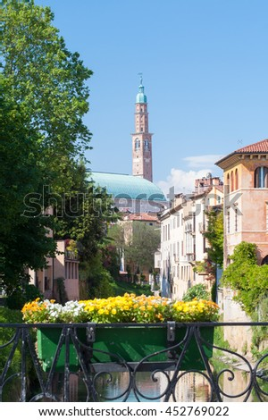 The clock tower and the palladian basilica in Vicenza, Italy, seen from the flowered Furo bridge on the retrone river