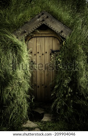The closed door of an old turf house in Iceland surrounded by long grass - stock photo
