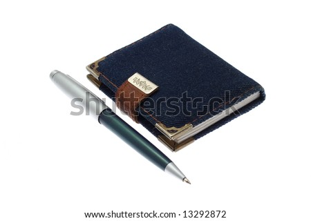 The closed notebook and ball pen on a white background