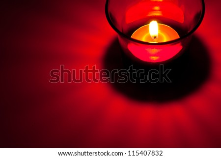 The closeup image of the burning red circular candle in the red glass - stock photo