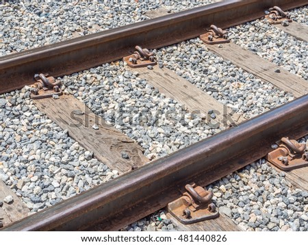 The closeup of an old railway tracks with wood and gravel