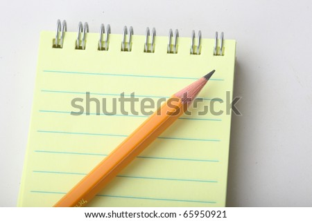 The closeup of notepad and yellow pencil on white background - stock photo