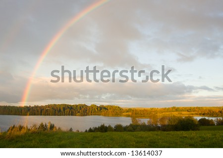 The cloudy sky and autumn rainbow above lake - stock photo