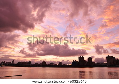 the cloudy sunset at the city nearby the river - stock photo