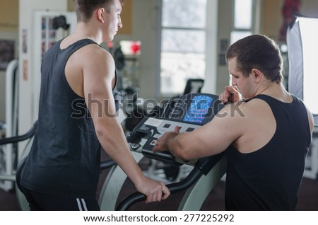 The coach helps the athlete on a treadmill at the gym - stock photo