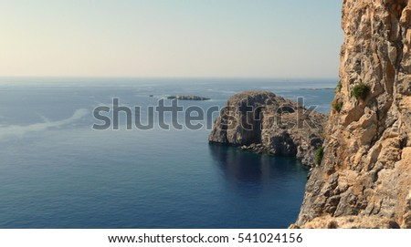The coast of Tilos island with blue sea and big stack, Greece