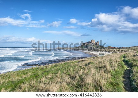 The coastal path leading to Bamburgh Castle in Northumberland - stock photo