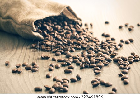 the coffee beans spill out of the sack - stock photo