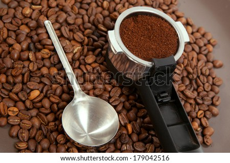 The coffee brewer handle against roasted coffee-bean - stock photo