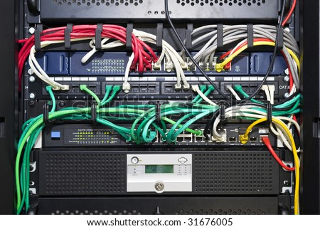 The color coded and neatly bracketed cables for network and telecommunications in an high tech server configuration - stock photo