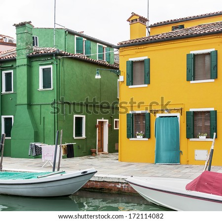 The colored houses on the shore of a narrow channel the Island of Burano - Venice, Italy
