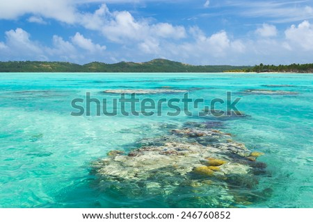 The colorful Aitutaki lagoon spotted by coral reef, in the middle of the South Pacific Ocean. Aitutaki atoll, Cook Islands. - stock photo
