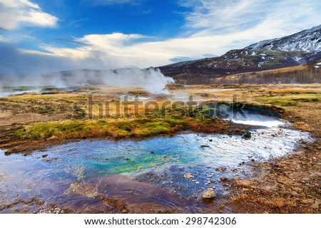 The colorful geyser landscape at the Haukadalur geothermal area, part of the golden circle route, in Iceland - stock photo