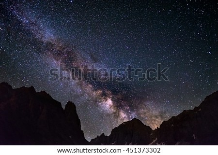 The colorful glowing core of the Milky Way and the starry sky captured at high altitude in summertime on the Alps. Scenic snowcapped mountain silhouette. - stock photo