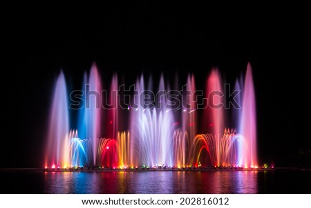 The colorful of fountain on the lake at night. - stock photo