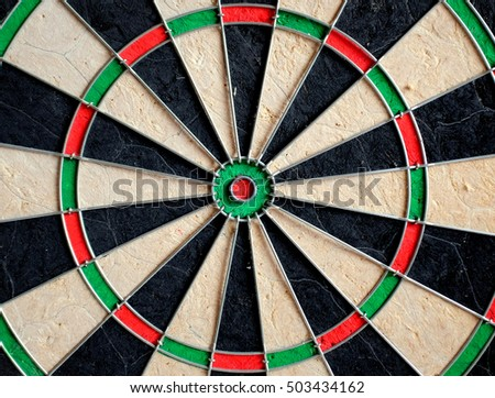 The colorful radiant middle of a dartboard with the bulls-eye and trebles depicting the sport of darts.