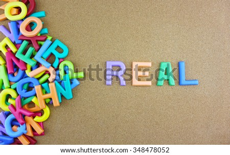 """The colorful word """"REAL"""" next to a pile of other letters over the brown board surface composition. - stock photo"""