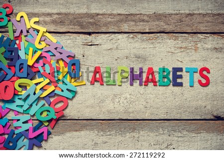 "The colorful words ""ALPHABETS"" made with wooden letters next to a pile of other letters over old wooden board. - stock photo"