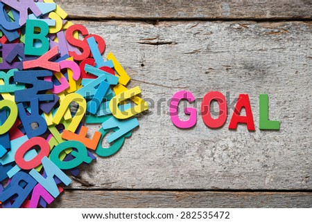 """The colorful words """"GOAL"""" made with wooden letters next to a pile of other letters over old wooden board.  - stock photo"""