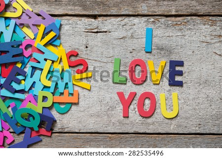 "The colorful words ""I LOVE YOU"" made with wooden letters next to a pile of other letters over old wooden board. - stock photo"