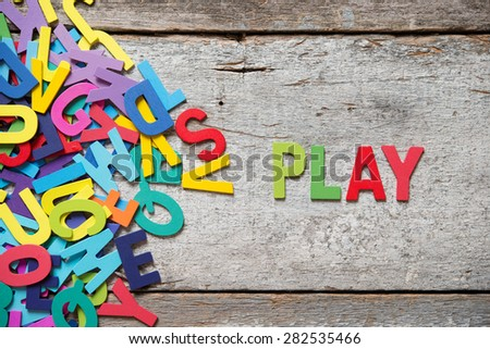 "The colorful words ""PLAY"" made with wooden letters next to a pile of other letters over old wooden board. - stock photo"