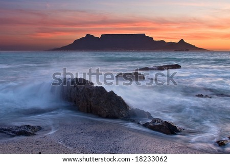 The colors of Table Mountain at sunset with large rock in foreground - stock photo