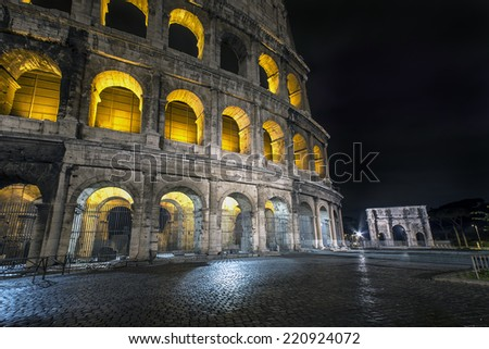 The Colosseum by night and the Arch of Constantine, Rome - stock photo