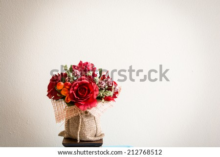 the colouful flowers with green leaves in the fabric jar - stock photo