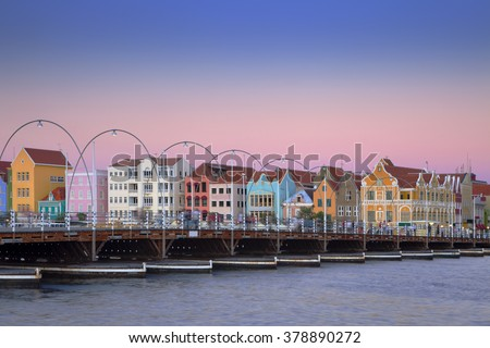 The coloured houses and the Queen Emma pontoon bridge of Willemstad, Curacao in the Netherlands Antilles at dusk. - stock photo