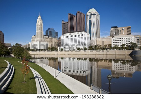 The Columbus, Ohio skyline reflected in the Scioto River.  Columbus is the capital of Ohio. - stock photo