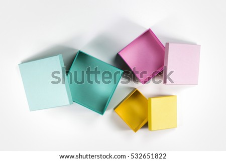 The Composition of Decorative Open Small Flat Box Pink, Yellow, Green on White Background.  Top View.