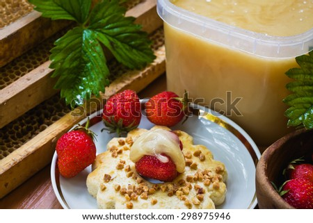 The composition of honey and strawberries in a retro style