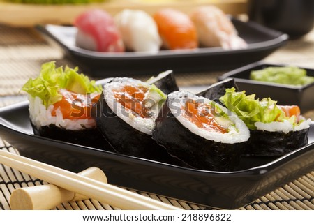 The composition of sushi - hosomaki with salmon, avocado and rice  - stock photo