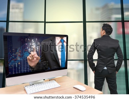 the computer on the wood table with Businessman point sign of money on the trading graph at the screen in front of the glass window over on the trading graph,Back side of Businessman