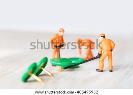 The concept of a collective solution to any problem. Miniature toy workers pressed thumbtacks in a wooden board. Close-up view. - stock photo