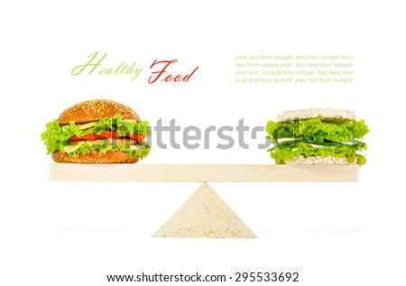 The concept of a healthy food, diet, losing weight. Classic burger and a healthy burger with wholegrain cereal crispbreads, vegetables, herbs and cheese on scales. Isolated on white background - stock photo